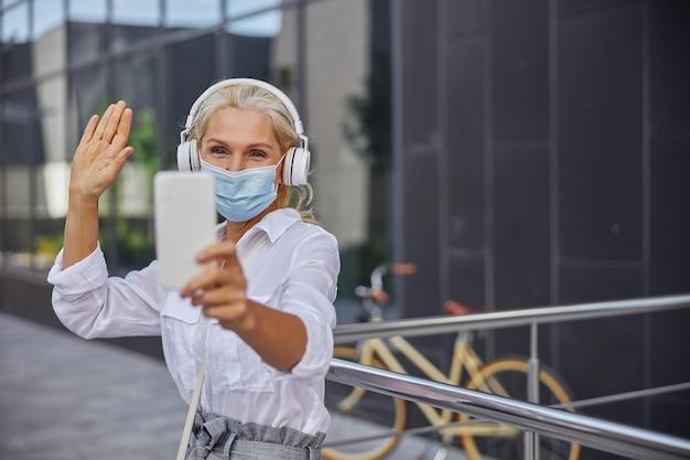 Nahaufnahme porträt einer fröhlichen frau im weißen hemd, die im freien steht und videoanrufe mit ihren freunden macht