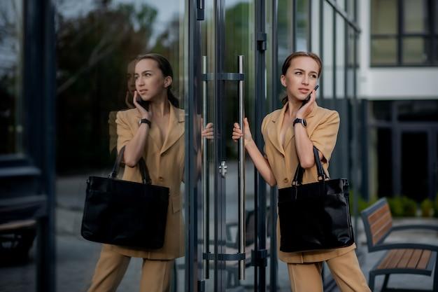 Nahaufnahme-porträt einer geschäftsfrau, die außerhalb des bürogebäudes steht und handy spricht.