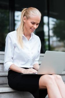 Nahaufnahme porträt einer jungen geschäftsfrau, die auf treppen sitzt und am laptop arbeitet