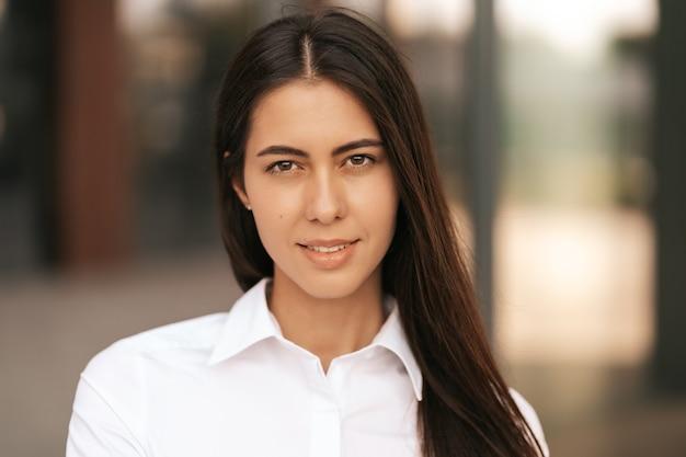 Nahaufnahme porträt einer kaukasischen hübschen geschäftsfrau, die lächelt, während sie auf unscharfem glasgebäude steht