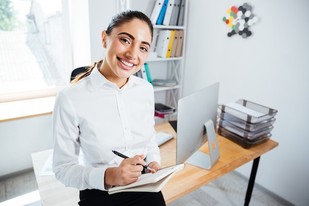 Nahaufnahme porträt einer lächelnden glücklichen geschäftsfrau, die sich notizen macht, während sie auf dem schreibtisch sitzt