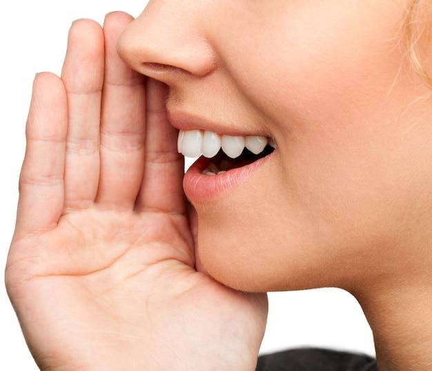 Nahaufnahme porträt einer lächelnden hautpflegefrau flüstert (erzählt) einen klatsch. Premium Fotos