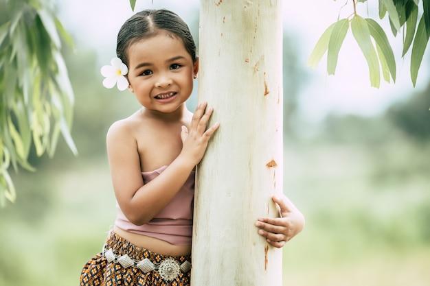 Nahaufnahme, porträt eines kleinen mädchens in traditioneller thailändischer kleidung und weiße blume auf ihr ohr legen, stehen und den baumstamm umarmen, lächeln, raum kopieren