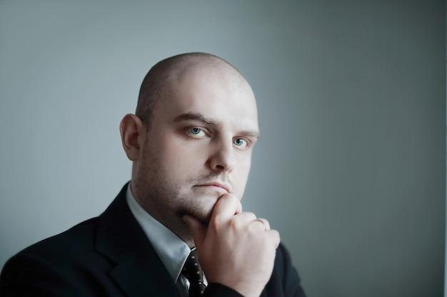 Nahaufnahme. porträt eines nachdenklichen geschäftsmannes auf grauem hintergrund.