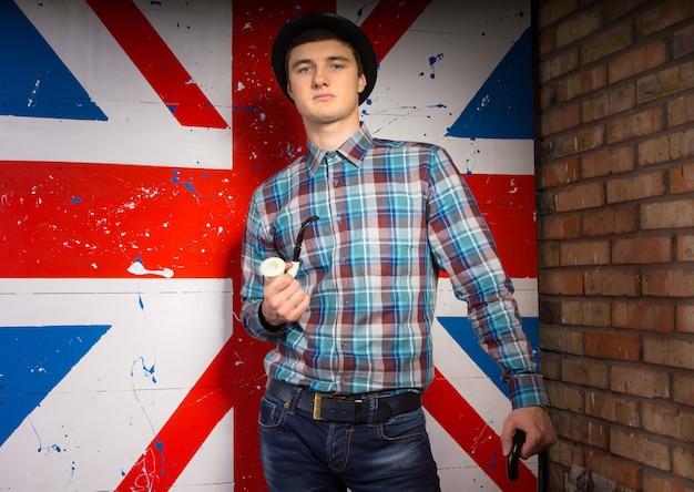 Nahaufnahme porträt eines wunderschönen jungen mannes in trendigem outfit mit tabakpfeife und stock vor dem britischen flaggendruck beim blick in die kamera.