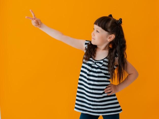 Nahaufnahme porträt kind mädchen bezaubernde fröhliche emotion gesichtsausdruck schönes lächeln hübsche junge tragen gestreiften kleid isoliert gelbe wand zeigt sieg finger, moderne kinder modern