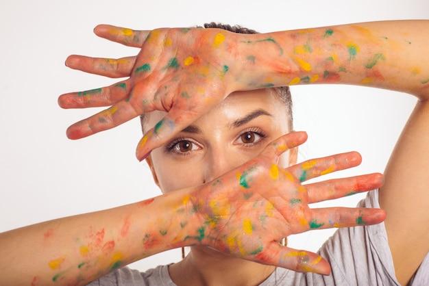 Nahaufnahme porträt teenager-mädchen bedeckt ihr gesicht mit ihren handflächen in farbe isoliert auf weiß