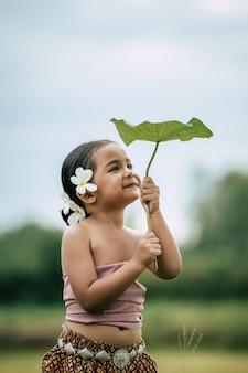 Nahaufnahme, porträt von hübschen kleinen mädchen in traditioneller thailändischer kleidung und weiße blume auf ihr ohr legen, stehen und auf lotusblatt in der hand schauen und glücklich auf reisfeld lächeln, platz kopieren