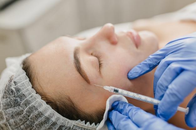 Nahaufnahme porträtinjektion auf gesicht der hübschen frau während botox-prozeduren im salon. professionelle arbeit, hände in blauen handschuhen, arzt, verjüngung, moderne medizin, schönheit machen, gesundheitswesen