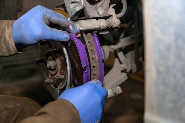 Nahaufnahme professioneller automechaniker, der die vorderen bremsbeläge im autoreparaturservice wechselt. autoworker-reparaturbremsen in der garage der reparatur-tankstelle