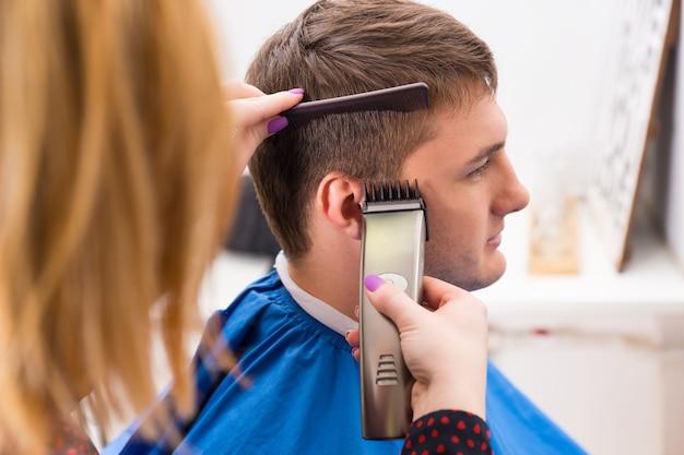 Nahaufnahme profil einer blonden stylistin mit lackierten fingernägeln mit elektrorasierer zum schneiden und stylen der haare junger männlicher kunden im salon