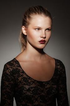 Nahaufnahme profilporträt eines schönen blonden mädchens mit haaren in einem pferdeschwanz, auf grauem dunklem hintergrund.