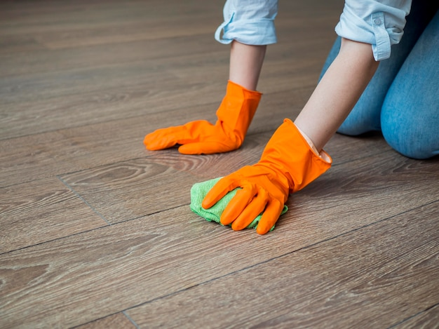 Nahaufnahme reinigung des bodens mit gummihandschuhen