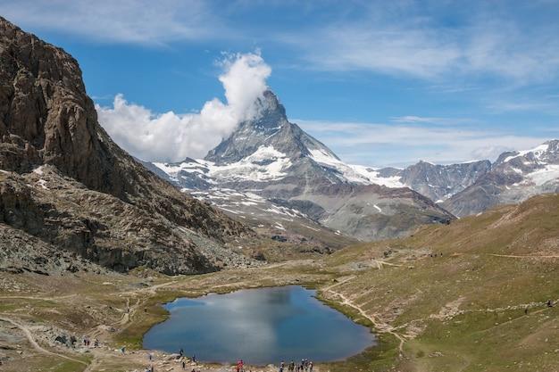 Nahaufnahme riffelsee see und matterhorn berg, szenen im nationalpark zermatt, schweiz, europa anzeigen. sommerlandschaft, sonnenscheinwetter, dramatischer blauer himmel und sonniger tag