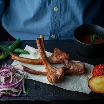 Nahaufnahme rippen gegrillte rippen auf fladenbrot mit ofenkartoffeln, paprika, tomaten, mit gehackten zwiebeln und sauce