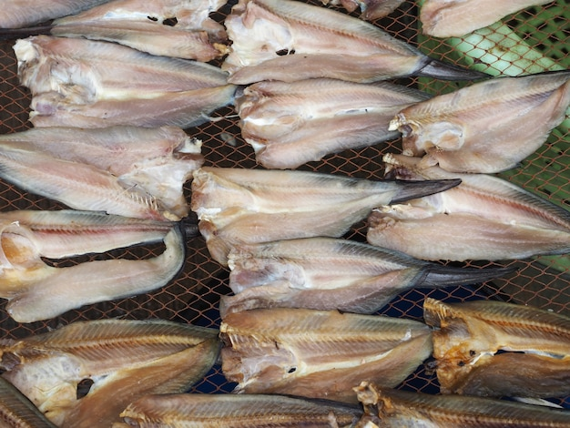 Nahaufnahme roher sonnengetrockneter fisch auf grill, traditionelle konservierte meeresfrüchte in thailand