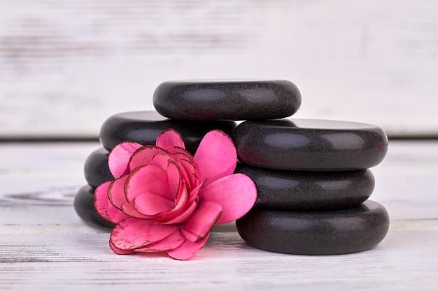 Nahaufnahme rosenblütenkopf und polierte steine für spa.