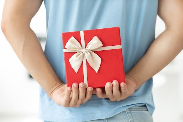 Nahaufnahme rückansicht des mannes im blauen t-shirt, das geschenkbox hinter seinem rücken hält, während