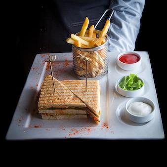 Nahaufnahme-sandwich mit bratkartoffeln und soße auf einem weißen teller am kellner