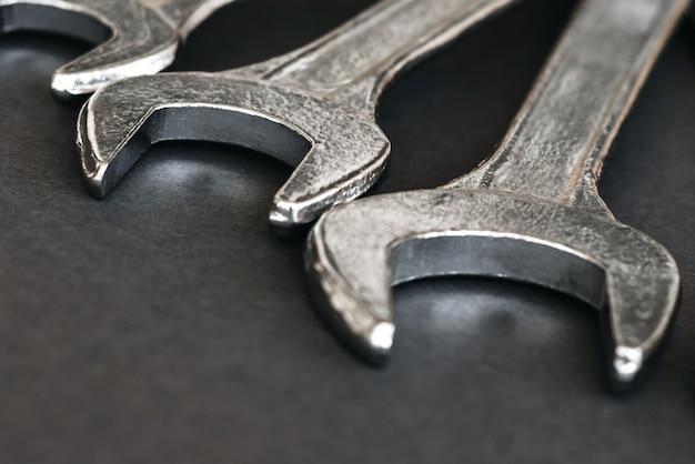 Nahaufnahme satz von chromschlüsseln oder schraubenschlüsseln isoliert auf grauem tisch.