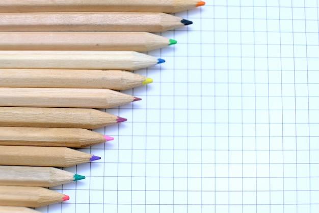 Nahaufnahme-satz von mehrfarbigen stiften auf dem karierten papierblatt des notizbuchs für die zeichnung. zurück zum schulkonzept.