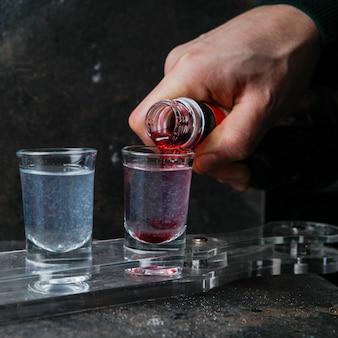 Nahaufnahme schnapsgläser mit farbgetränken auf einem glas