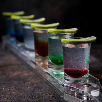 Nahaufnahme schnapsgläser mit farbgetränken und limette auf einem glas