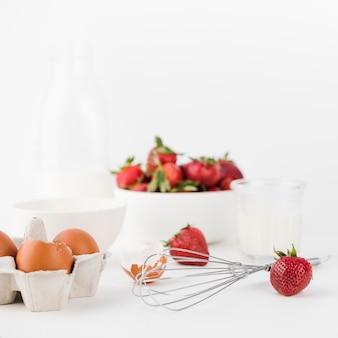 Nahaufnahme schneebesen mit erdbeeren und eiern