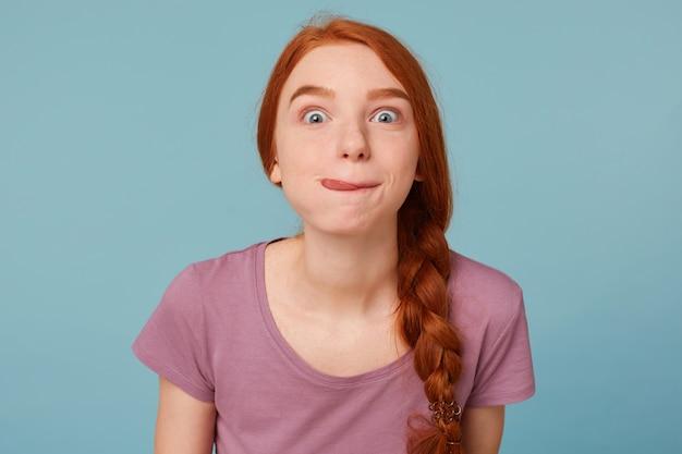 Nahaufnahme schöne rothaarige frau mit ihren geflochtenen haaren hat lustige blicke auf die vorderseite gekleidet in ein lässiges t-shirt