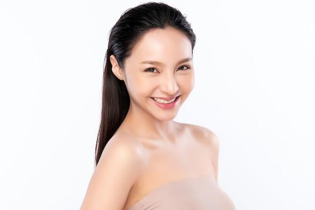 Nahaufnahme schönheitsgesicht. lächelnde asiatische frau, die gesundes hautporträt berührt. schönes glückliches mädchenmodell mit frisch glühender hydratisierter gesichtshaut und natürlichem make-up
