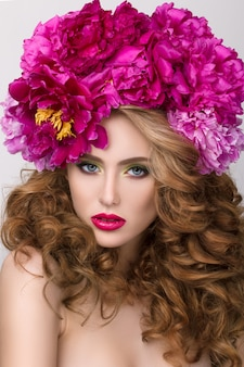 Nahaufnahme-schönheitsporträt des jungen hübschen mädchens mit blumenkranz in ihrem haar, das hellen rosa lippenstift trägt. helles modernes sommer make-up.
