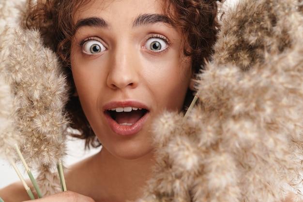 Nahaufnahme schönheitsporträt einer attraktiven aufgeregten jungen topless frau mit kurzen lockigen braunen haaren isoliert über weißer wand, mit getrockneten kräutern