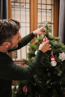 Nahaufnahme schoss den älteren mann, der weihnachtsbaum verziert