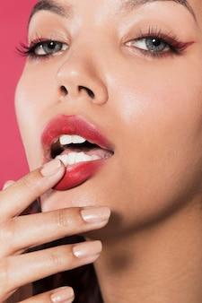 Nahaufnahme schoss die junge frau, die ihre roten lippen berührt