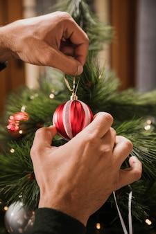 Nahaufnahme schoss die person, die weihnachtsbaum verziert