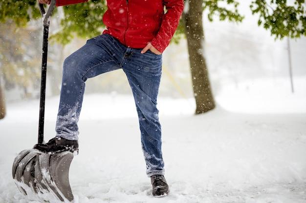 Nahaufnahme schoss für einen mann mit seinem fuß auf der schneeschaufel, während er in einem schneebedeckten feld steht