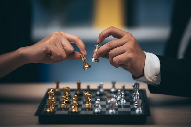 Nahaufnahme schoss goldenes schach, um silberkönigschach auf weißem und schwarzem schachbrett für business challenge-gewinner und verlierer-konzept zu besiegen