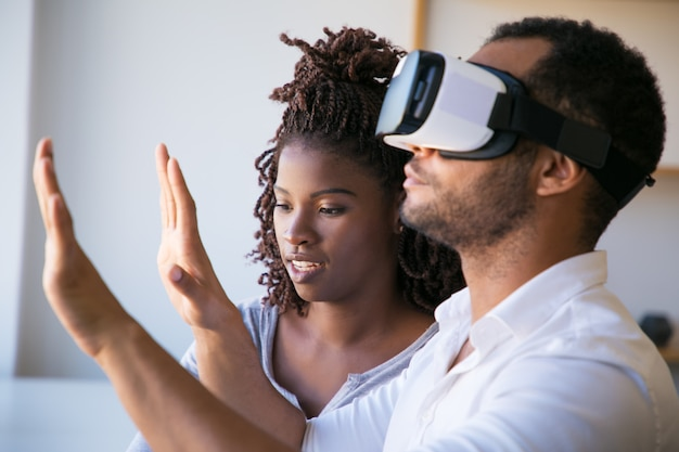 Nahaufnahme schoss vom mann, der kopfhörer der virtuellen realität prüft