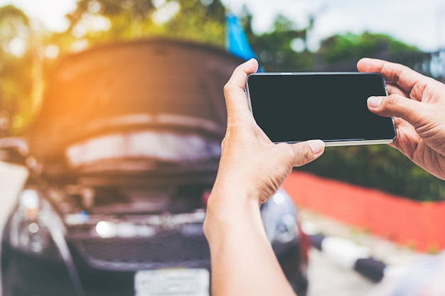 Nahaufnahme schoss vom mann, der smartphone mit lokalisiertem schirm nach autounfall verwendet