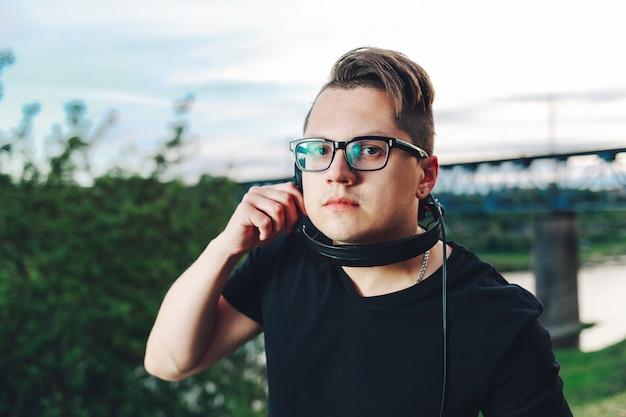 Nahaufnahme schoss vom zufälligen jungen mann in den hippie-gläsern mit kopfhörern auf dem sommernaturhintergrund