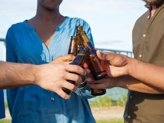 Nahaufnahme schoss von den freunden, die bierflaschen klirren. gruppe junge leute, die sich nach der arbeit entspannen. feier-konzept