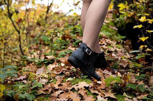 Nahaufnahme schoss von den schönen weiblichen beinen in den schwarzen schuhen, die im wald auf abgenutzte blätter und moos im herbst stehen