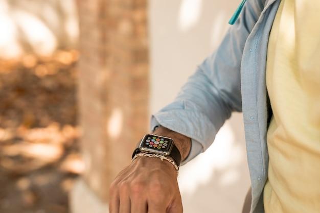 Nahaufnahme schoss von einem mann, der sein smartwatch überprüft