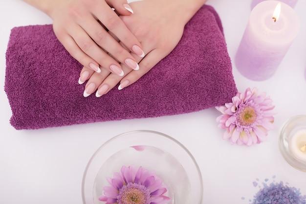 Nahaufnahme schoss von einer frau in einem nagelsalon, der eine maniküre von einem kosmetiker mit watte mit aceton empfängt. frau, die nagelmaniküre erhält. kosmetikerin datei nägel an einen kunden