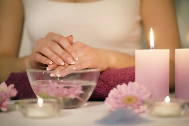 Nahaufnahme schoss von einer frau in einem nagelsalon, der eine maniküre von einem kosmetiker mit watte mit aceton empfängt. frau, die nagelmaniküre erhält.