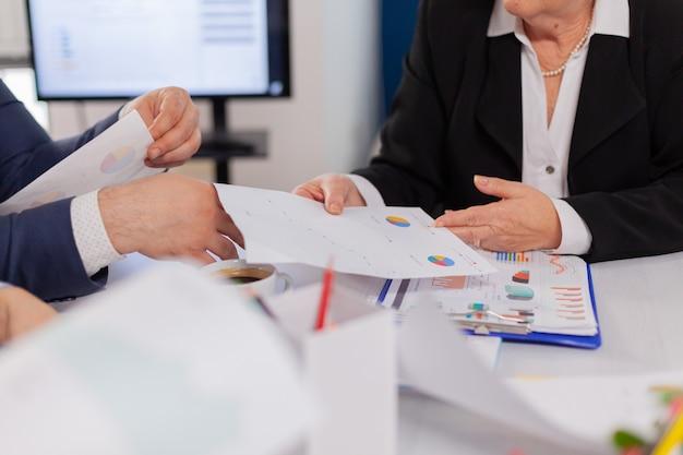Nahaufnahme schreibtisch voller papierstatistiken in diagrammen und verschiedenen geschäftsleuten