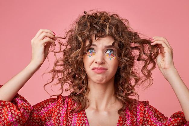 Nahaufnahme schuss der jungen frau, die nach oben schaut, lockiges haar zieht und traurig ist, grimasse macht, enttäuschung zeigt