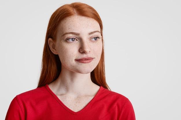 Nahaufnahme schuss der nachdenklichen konzentrierten sommersprossigen ingwerfrau mit glattem langem haar