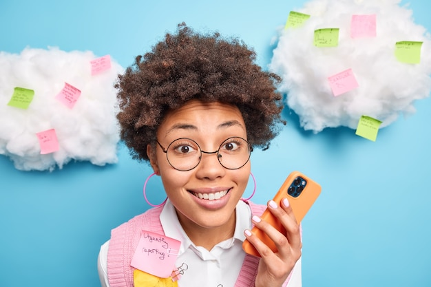 Nahaufnahme schuss der schönen neugierigen weiblichen büroangestellten lächelt glücklich hält handy-checks newsfeed umgeben von bunten aufklebern mit schriftlichen informationen oder liste zu tun