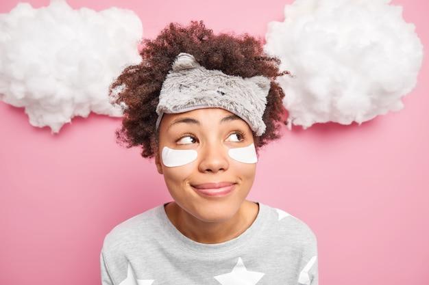Nahaufnahme schuss der verträumten niedlichen lockigen frau schaut nachdenklich beiseite denkt an etwas angenehmes trägt schlafmaske auf der stirn nachtwäsche genießt guten morgen und beginn des neuen tages